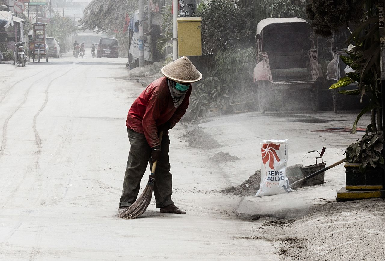 A man sweeping up ash volcanic ash in Yogyakarta; Indonesaia, during the 2014 eruption of Kelud.